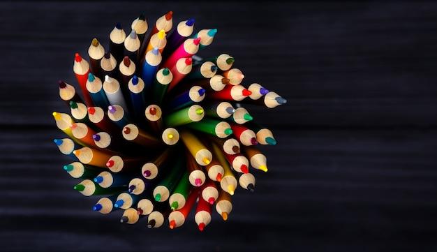 Crayons colorés dans un support en métal sur une table en bois noire