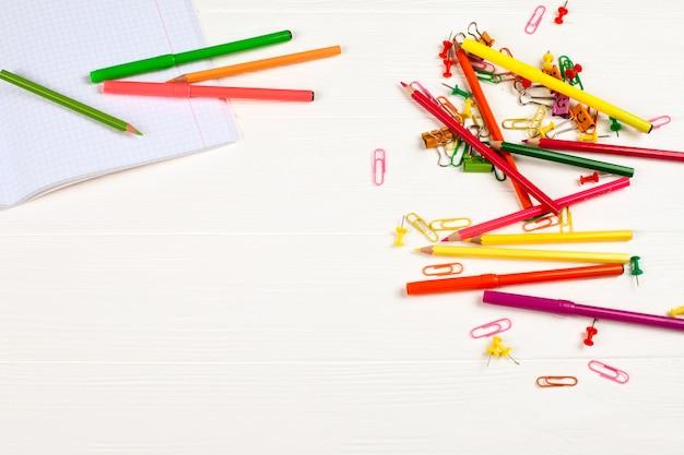 Crayons colorés et feutres, papier à lettres et papeterie sur fond en bois blanc.