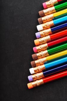Crayons colorés avec gommes d'affilée sur fond noir. vue de dessus, espace libre