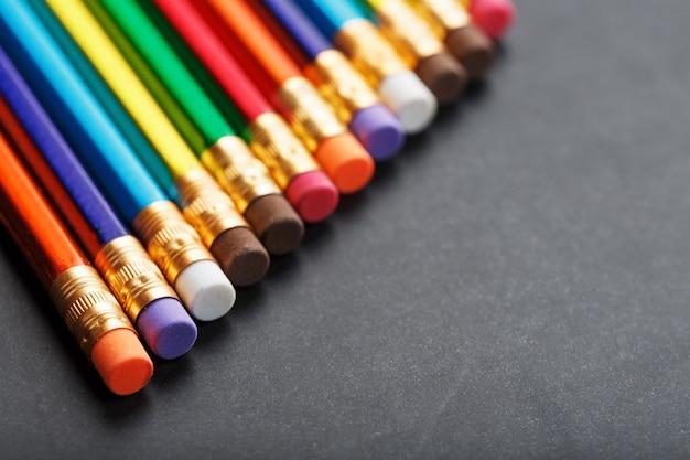 Crayons colorés avec gommes d'affilée sur fond noir