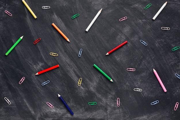 Crayons colorés et trombones sur tableau noir