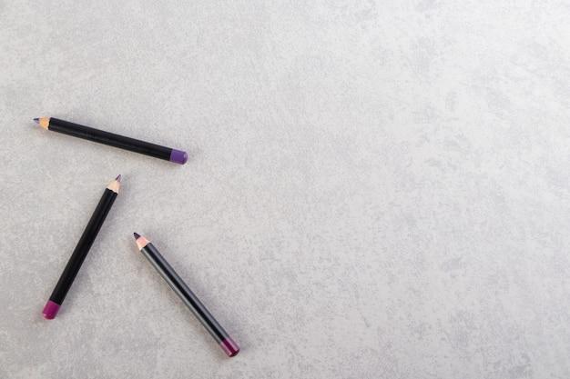 Crayons cosmétiques de maquillage placés sur une table en pierre.
