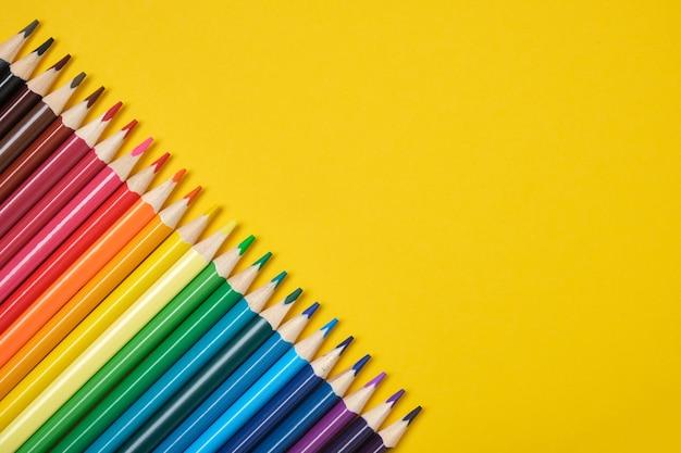 Crayons de couleur alignés en diagonale sur un espace de copie de fond jaune