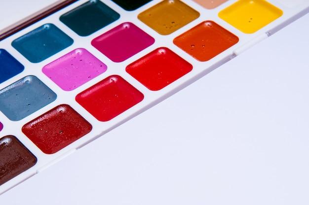 Crayons de couleur et aquarelles sur blanc, retour à l'école, papeterie avec espace vide