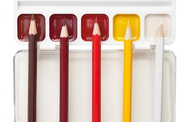 Crayons de couleur et aquarelles isolés sur fond blanc
