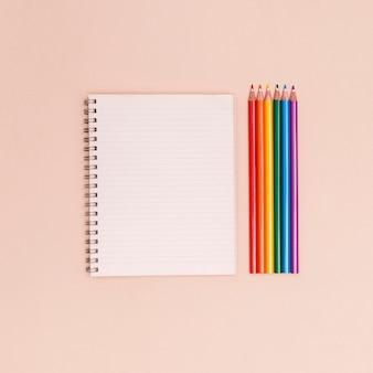 Crayons de couleur arc en ciel et cahier