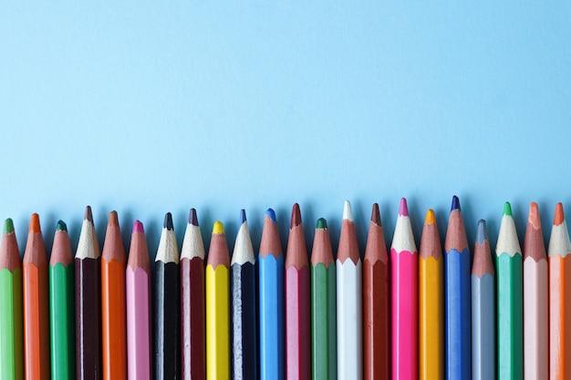 Crayons de couleur sur bleu, espace copie.