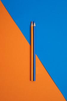 Crayons de couleur bleu et orange coincés isolés sur une table orange et bleue