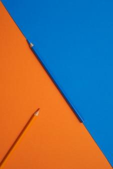 Crayons de couleur bleu et orange isolés sur une table orange et bleue