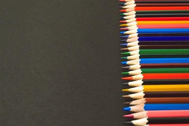 Crayons de couleur bordés d'affilée sur un fond noir
