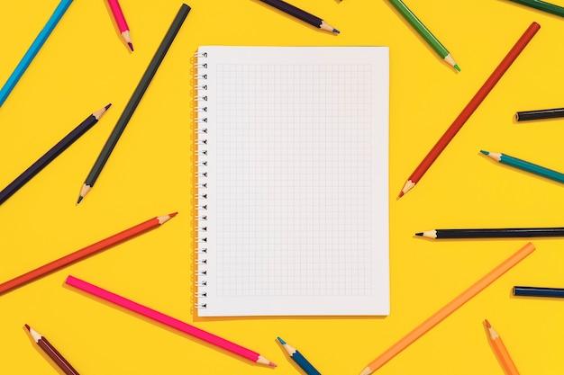 Crayons de couleur et cahier sur fond jaune