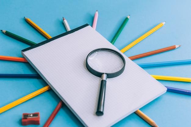 Crayons de couleur avec un cahier et une loupe sur fond bleu