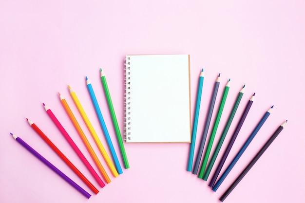 Crayons de couleur et cahier sur mur clair.