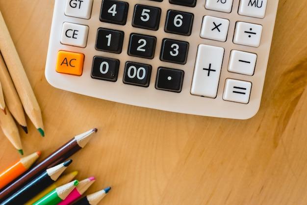 Crayons de couleur et calculatrice sur une table.