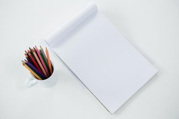 Crayons de couleur conservés dans une tasse avec bloc-notes