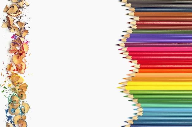 Crayons de couleur avec des copeaux de crayon de couleur sur fond blanc