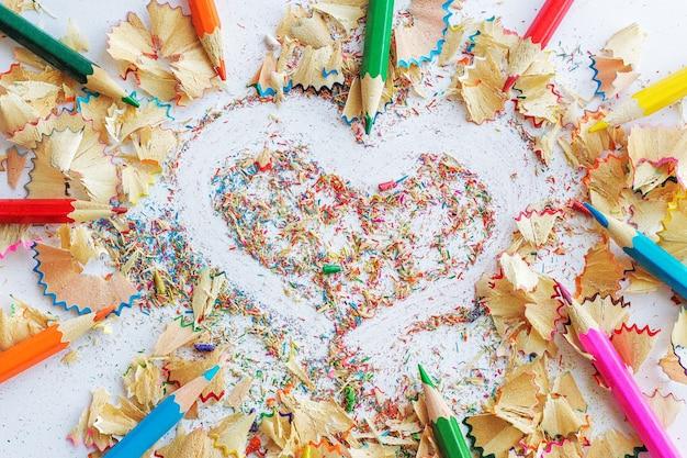 Crayons de couleur et copeaux de crayons, dessin de cœur.