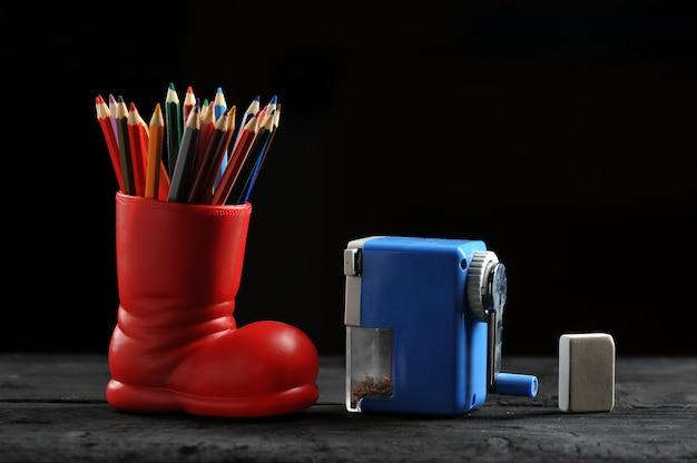 Crayons de couleur dans des bottes rouges, un taille-crayon et une gomme
