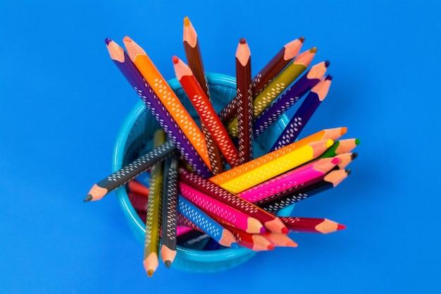 Crayons de couleur dans un étui à crayons sur fond bleu, vue du dessus.