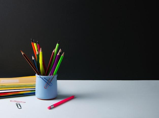 Crayons de couleur dans un support bleu sur fond noir et bleu avec espace de copie.