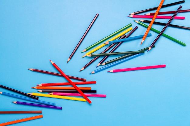 Crayons de couleur dispersés en diagonale sur fond bleu. mise à plat, vue de dessus