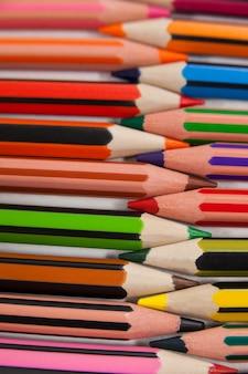 Crayons de couleur disposés en motif imbriqué sur fond blanc