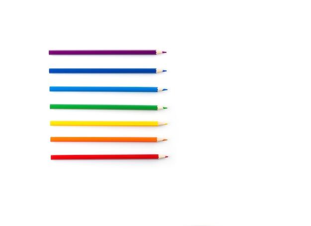 Crayons de couleur disposés selon la couleur de l'arc-en-ciel sur fond blanc