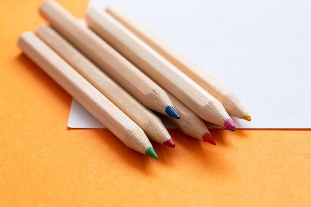 Crayons de couleur avec du papier sur orange