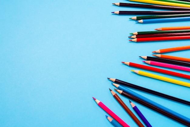 Crayons de couleur éparpillés sur fond bleu