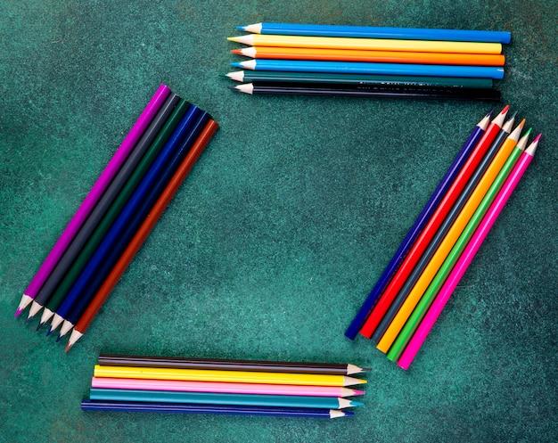 Crayons de couleur de l'espace copie vue de dessus sur fond vert