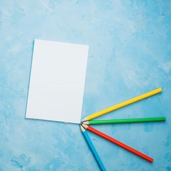 Crayons de couleur et feuille de papier blanc sur fond bleu