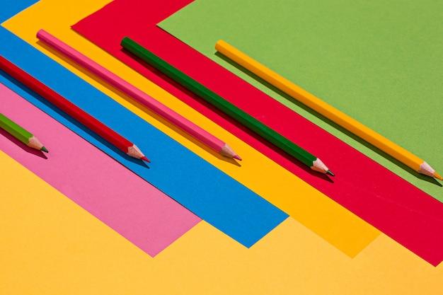 Crayons de couleur et feuilles de papier de couleur