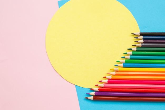 Crayons de couleur et figures géométriques sur mur clair.