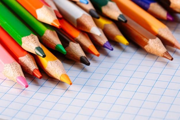 Crayons de couleur sur fond blanc. espace libre pour le texte. outils pour le dessin, l'éducation, l'école, la créativité. feuille du cahier sur la table.
