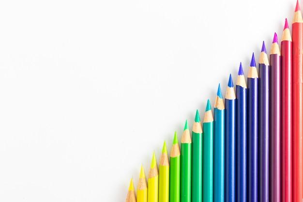 Crayons de couleur sur fond blanc triés par couleurs et en diagonale