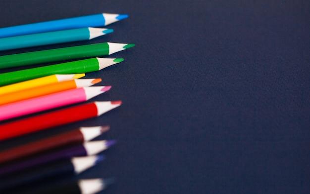Crayons de couleur sur fond bleu foncé.