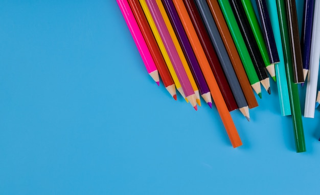 Crayons de couleur sur fond bleu, fournitures scolaires