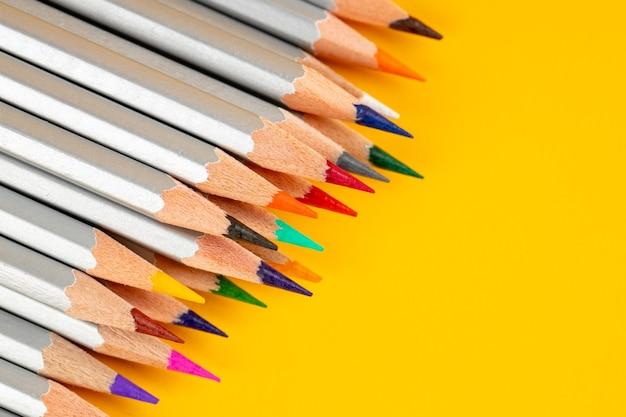 Un crayons de couleur sur fond jaune. toile de fond de papeterie abstraite