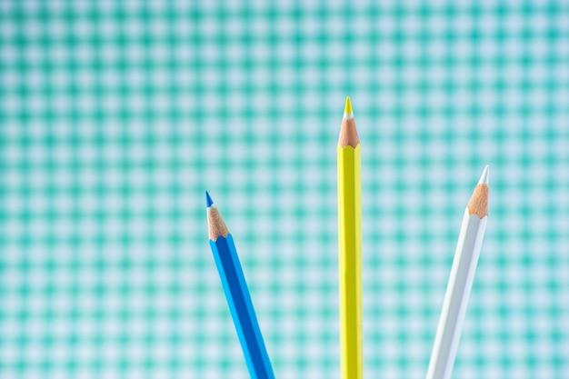 Crayons de couleur sur fond pastel dans une cage avec un espace pour le texte.