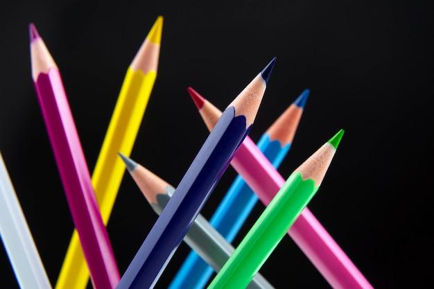 Crayons de couleur sur fond sombre. éducation et créativité. loisirs et art