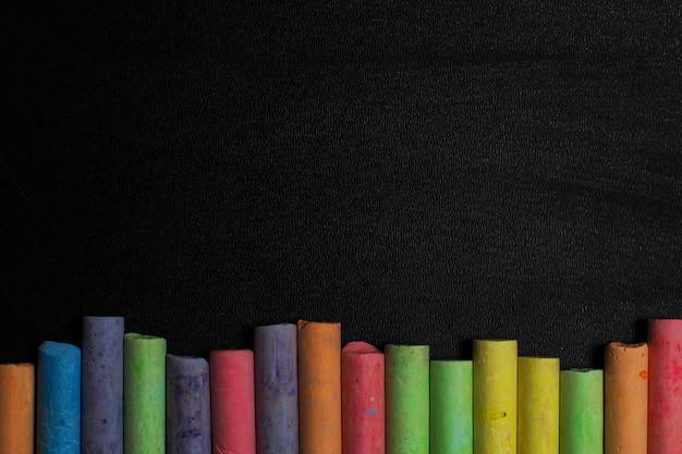 Crayons de couleur sur un fond de tableau noir.