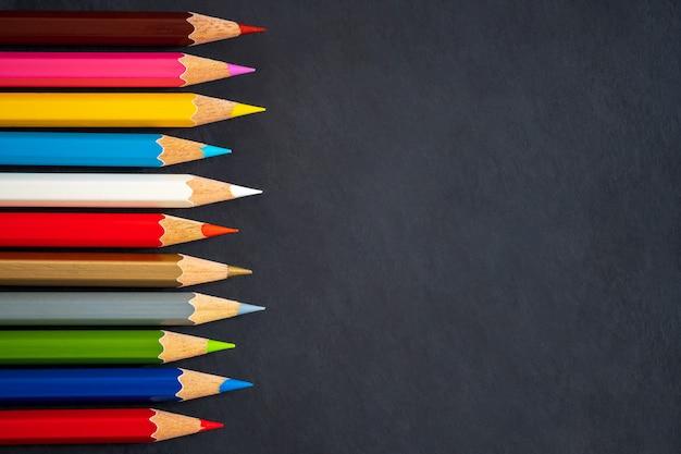 Crayons de couleur sur fond de tableau