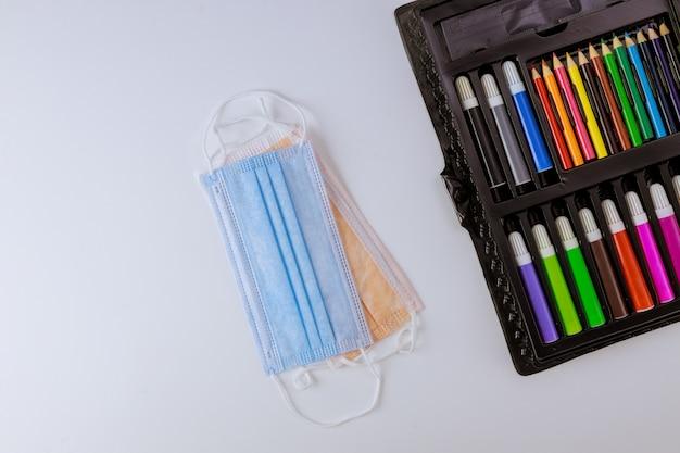 Crayons de couleur fournitures de bureau de l'école d'art avec des masques hygiéniques médicaux sûrs pour le coronavirus scolaire covid-19 pandémie