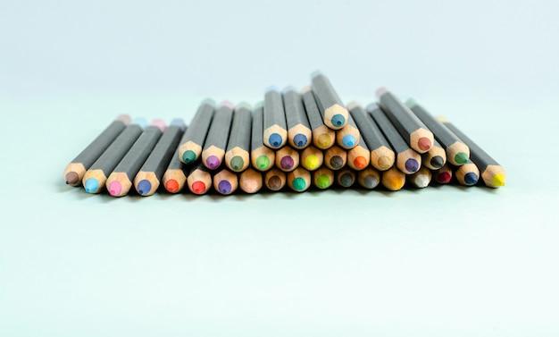 Crayons de couleur sur un gros plan de fond bleu.