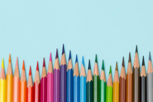 Crayons de couleur isolés sur fond bleu.