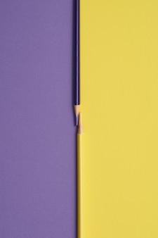 Crayons de couleur jaune et violet isolés sur un tableau violet et jaune