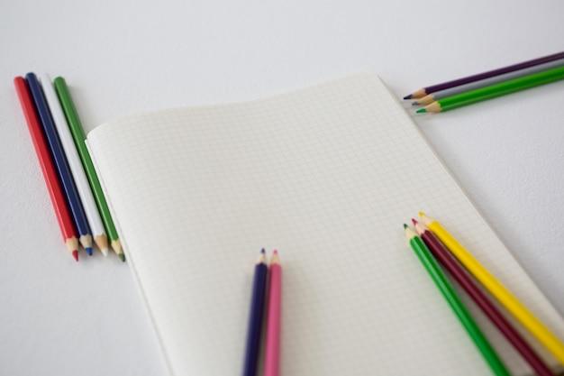 Crayons de couleur avec livre