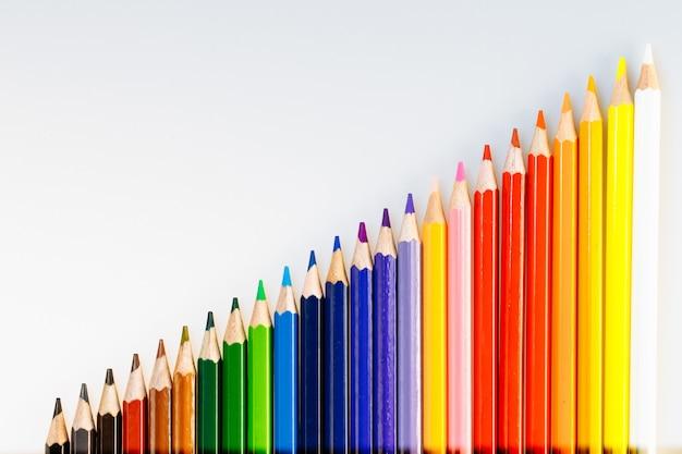Crayons de couleur sur mur blanc crayons pour usage scolaire ou professionnel. instruments de dessin pour créer des images