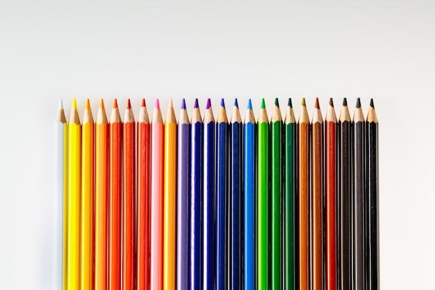 Crayons de couleur sur mur blanc. crayons à usage scolaire ou professionnel. instruments de dessin pour créer des images