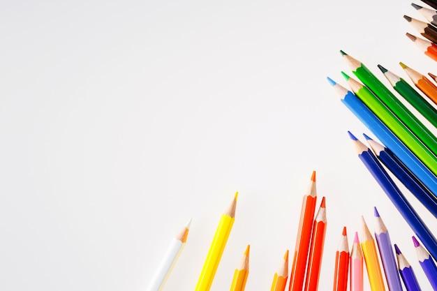 Crayons de couleur sur le mur blanc espace libre pour le texte. outils pour le dessin, l'éducation, l'école, la créativité.